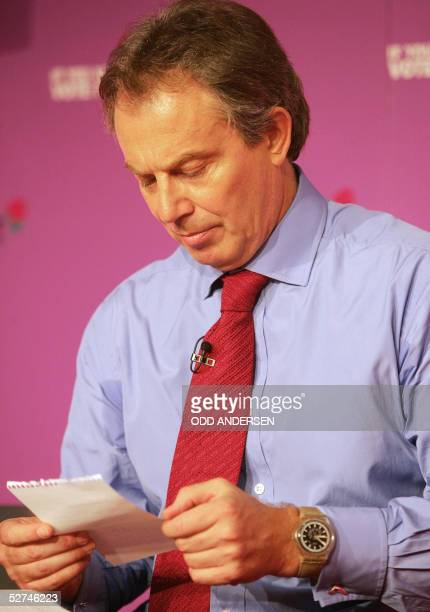 Britain's Prime minister Tony Blair reads a note 02 May 2005 in London the note was handed to the Prime minister during a press conference to inform...