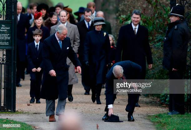 Britain's Prince Andrew Duke of York stoops to pick up the hat of a wellwisher next to Britain's Prince Charles Prince of Wales as they lead other...