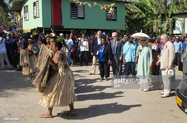 Britain's Prince Charles and his wife Camilla watch traditional dancers at Boera Village some 20kms west of Port Moresby on November 4 2012 Papua New...