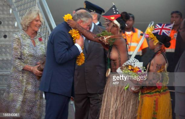 Britain's Prince Charles and wife Camilla are presented with flowers after arriving at Port Moresby's Jackson's International Airport on November 3...