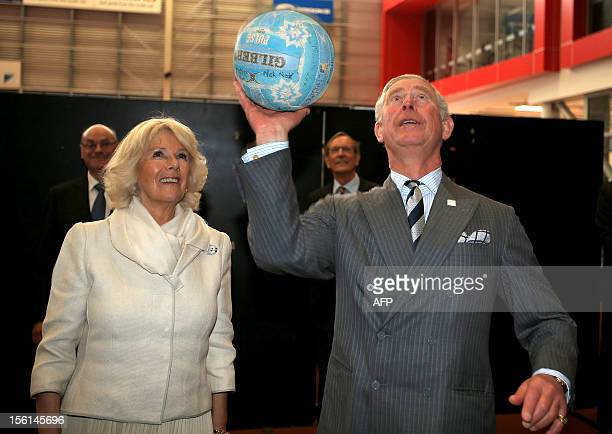 Britain's Prince Charles attempts a netball shot as his wife Camilla looks on after meeting the New Zealand Silver Ferns netball team at the...