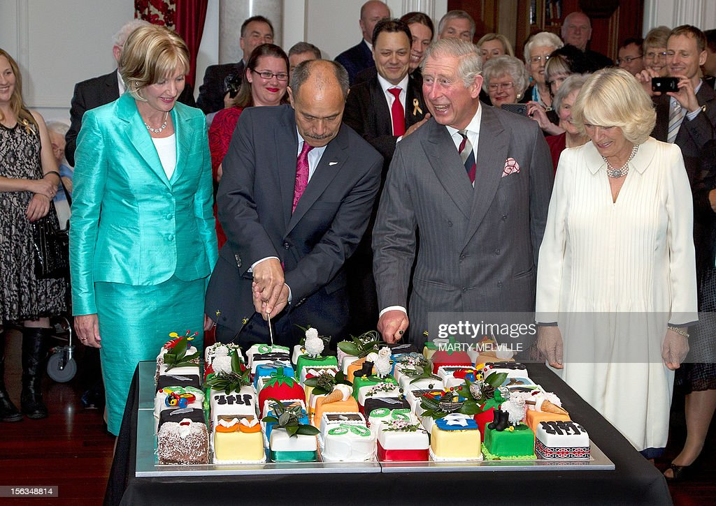 Britain's Prince Charles (2nd-R), his wife Camilla (R), the Governor General of New Zealand Lt General Jerry Mateparae (2nd-L) and his wife Lady Janine Mateparae stand in front of the birthday cake during a birthday party for Prince Charles at Government House in Wellington on November 14, 2012. The Royal couple are in New Zealand on the last leg of a Diamond Jubilee that takes in Papua New Guinea, Australia and New Zealand. AFP PHOTO / Marty Melville