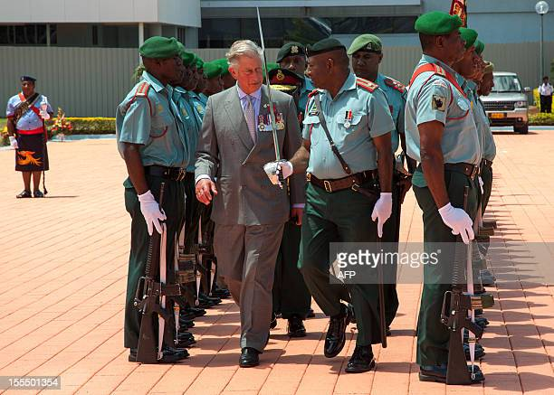 Britain's Prince Charles inspects a Guard of Honour as he and his wife prepare to leave Jacksons International Airport in Port Moresby on November 5...
