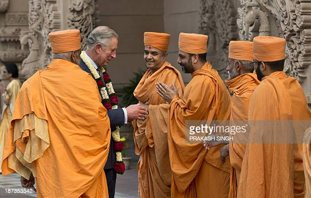 Britain's Prince Charles interacts with priests during a visit to the Akshardham temple in New Delhi on November 8 2013 Britain's Prince Charles is...