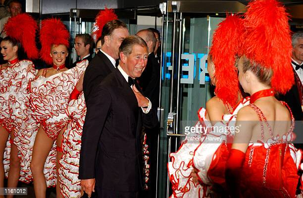 Britain's Prince Charles is greeted by CanCan girls as he arrives at the premiere of Moulin Rouge September 3 2001 in London England