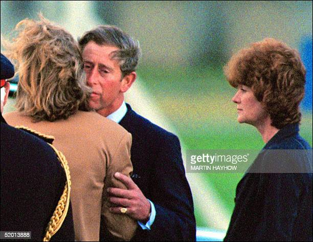 Britain's Prince Charles kisses Lady Sarah McCorquiodale while her sister Lady Jane Fellows looks on at RAF Northolt Airport near London 31 AUG...