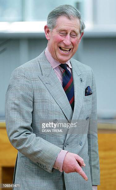 Britain's Prince Charles laughs at a Merino sheep he just sheared with a pair of hand shears during a visit to Moutere Sheep Station in Alexandra...