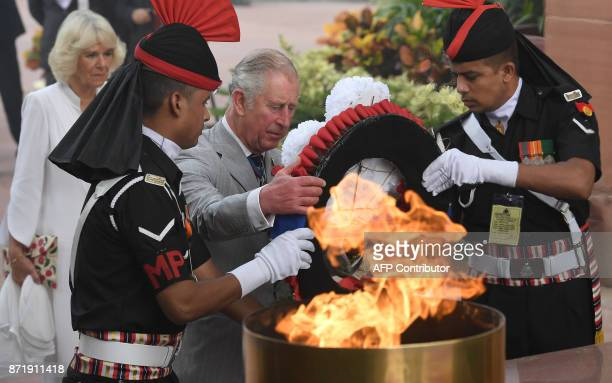 Britain's Prince Charles lays a wreath as his wife Camilla Duchess of Cornwall looks on as they pay tribute at the Amar Jawan Jyoti war memorial in...