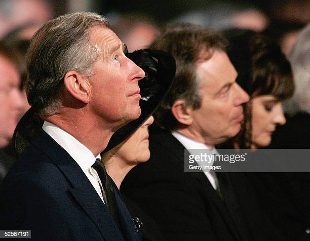 Britain's Prince Charles looks up as he sits with Camilla Parker-Bowles , Britain's Prime Minister Tony Blair and his wife Cherie attend a service in...