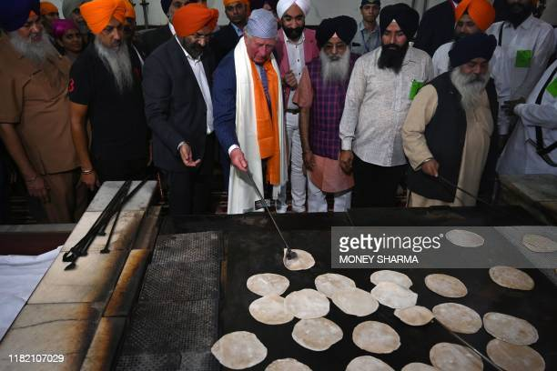 Britain's Prince Charles make chapati bread at a community kitchen as he visits the Gurudwara Bangla Sahib, a prominent Sikh house of worship, in New...