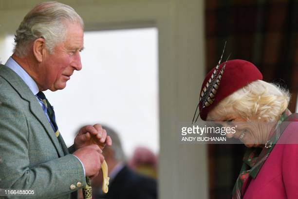 Britain's Prince Charles Prince of Wales and Britain's Camilla Duchess of Cornwall gesture during the annual Braemar Gathering in Braemar central...