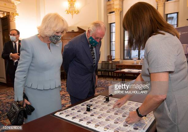Britain's Prince Charles, Prince of Wales and Britain's Camilla, Duchess of Cornwall, both wearing a face mask or covering due to the COVID-19...