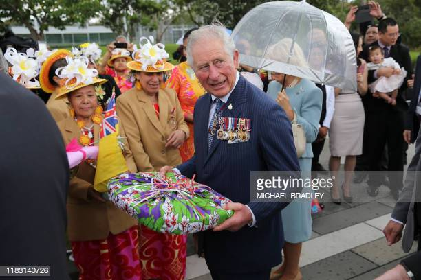 Britain's Prince Charles, Prince of Wales and Camilla, Duchess of Cornwall receives gifts after they laid a wreath at Mt Roskill War Memorial Park in...