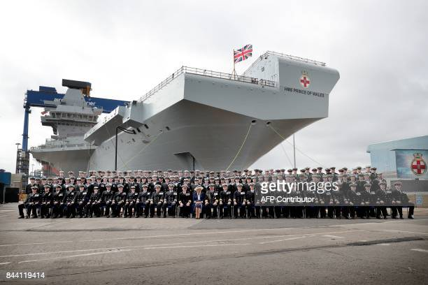Britain's Prince Charles Prince of Wales and Camilla Duchess of Cornwall pose for an official picture with the ship's company during the official...