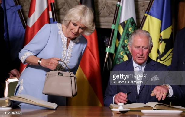 Britain's Prince Charles Prince of Wales and his wife Britain's Camilla Duchess of Cornwall sign the guest book at the city hall in Leipzig eastern...