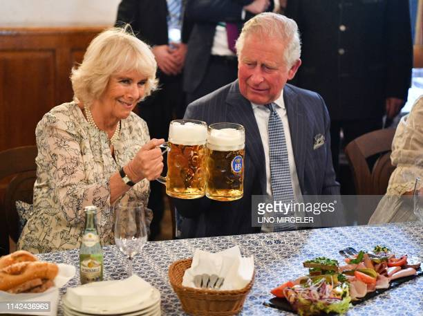 Britain's Prince Charles, Prince of Wales and his wife Britain's Camilla, Duchess of Cornwall, clink their beer glasses as they visit the...