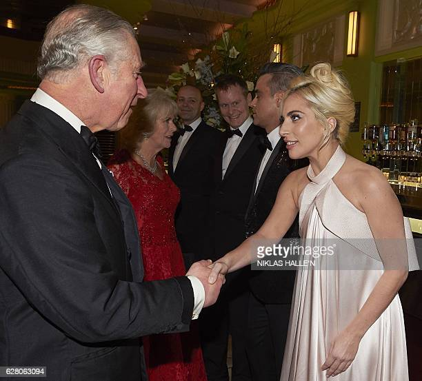 Britain's Prince Charles Prince of Wales and his wife Britain's Camilla Duchess of Cornwall react as they greet British singer Robbie Williams and US...