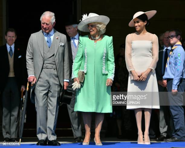 Britain's Prince Charles Prince of Wales and his wife Britain's Camilla Duchess of Cornwall and Britain's Meghan Duchess of Sussex listen as her...