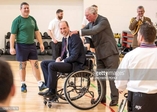 TOPSHOT Britain's Prince Charles Prince of Wales consoles his son Britain's Prince William Duke of Cambridge after he threw a basketball from a...