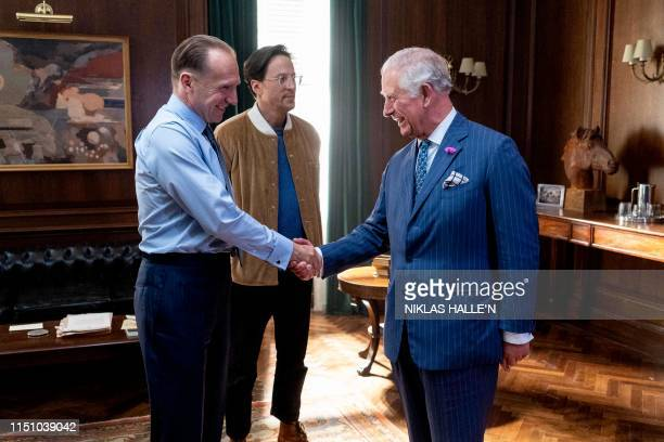 Britain's Prince Charles Prince of Wales greets British actor Ralph Fiennes and US Director Cary Joji Fukunaga as he tours the set of the 25th James...