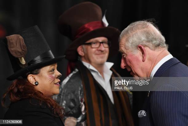 Britain's Prince Charles Prince of Wales greets performers from the immersive theatre production The Alice Experience as he arrives for a visit to St...