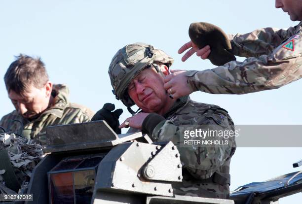 Britain's Prince Charles Prince of Wales has his helmet adjusted after taking a ride on a Warrior Tracked Armoured Vehicle during a training exercise...
