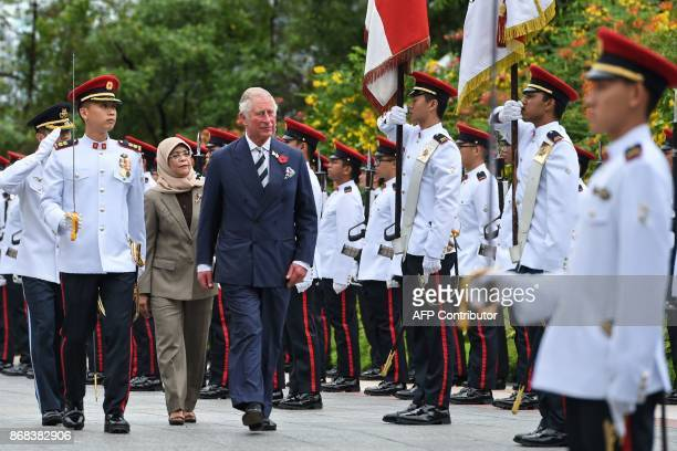 Britain's Prince Charles Prince of Wales is accompanied by Singapore's President Halimah Yacob during a welcoming ceremony at the Istana presidential...
