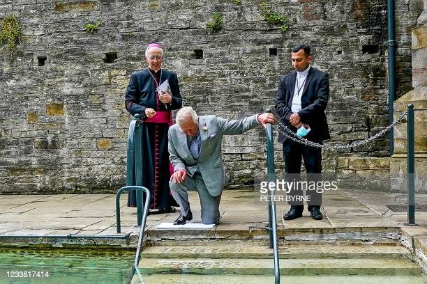 Britain's Prince Charles, Prince of Wales kneels as he prepares to touch the healing water as Bishop of Wrexham Peter Brignall and Roman Catholic...