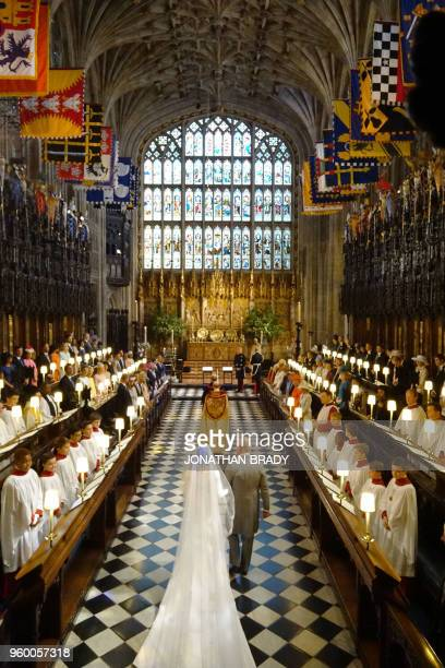 Britain's Prince Charles, Prince of Wales leads US fiancee of Britain's Prince Harry, Meghan Markle up the aisle of St George's Chapel for the...