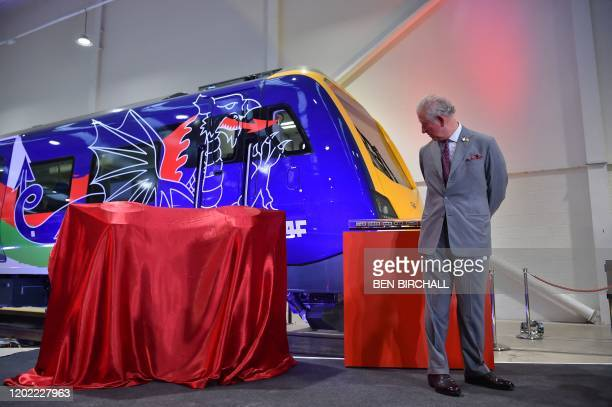 TOPSHOT Britain's Prince Charles Prince of Wales looks at a model train presented to him during a visit to the CAF train factory in Newport Wales on...