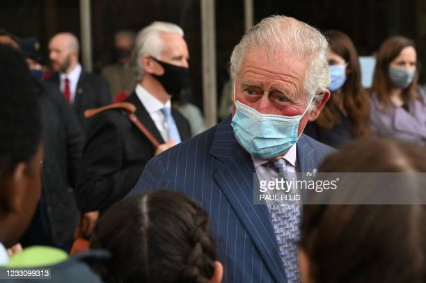 Britain's Prince Charles, Prince of Wales meets school children during a visit to Coventry Cathedral in Coventry, central England on May 25 during...