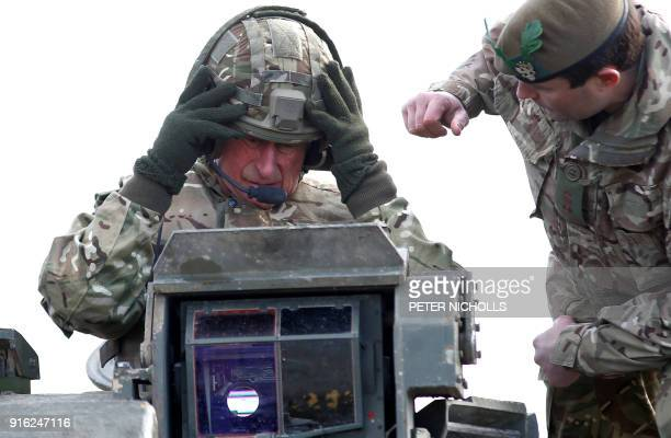 Britain's Prince Charles Prince of Wales puts on a helmet before he rides on a Warrior Tracked Armoured Vehicle during a training exercise whilst on...