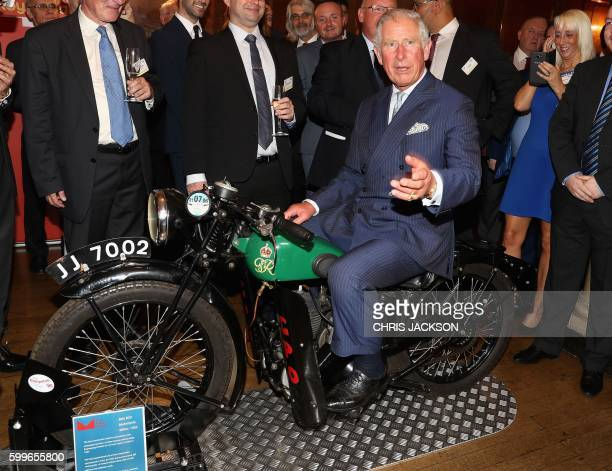 Britain's Prince Charles Prince of Wales reacts as he sits on a BSA 500cc motorbike used for delivering telegrams during a reception to mark the...