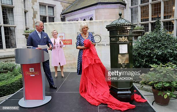 Britain's Prince Charles Prince of Wales reacts as his wife Britain's Camilla Duchess of Cornwall unveils a replica of a green Penfold Postbox during...