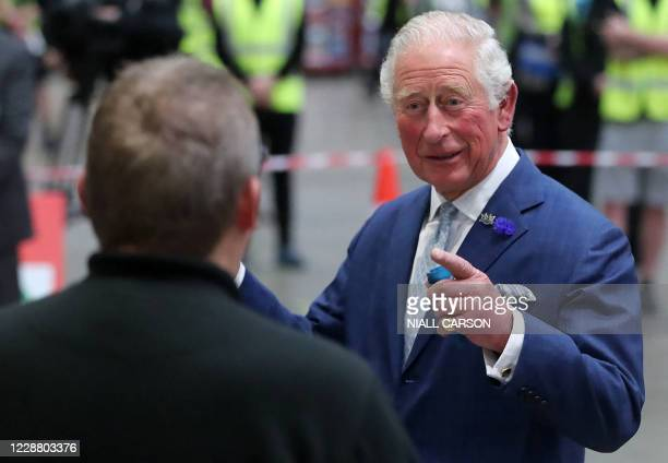 Britain's Prince Charles, Prince of Wales shares a joke with driver Stephen Taggart during a visit to Henderson Foodservice's food and grocery...