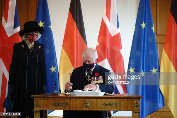 Britain's Prince Charles , Prince of Wales signs the guests book next to Camilla, Duchess of Cornwall prior a meeting at the presidential Bellevue...