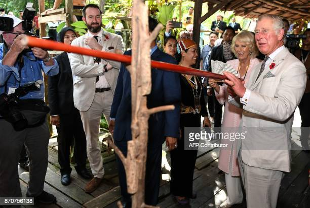 Britain's Prince Charles Prince of Wales smiles after trying a blowpipe a weapon of the indigenous people of Sarawak as Camilla Duchess of Cornwall...