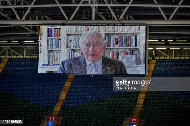 Britain's Prince Charles, Prince of Wales speaks via video link on a large screen with a recorded message during the official opening of the new...