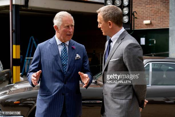 Britain's Prince Charles Prince of Wales speaks with British actor Daniel Craig as he tours the set of the 25th James Bond Film at Pinewood Studios...