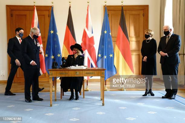 Britain's Prince Charles , Prince of Wales stands next to Camilla , Duchess of Cornwall as she signs the guests book next to German President...