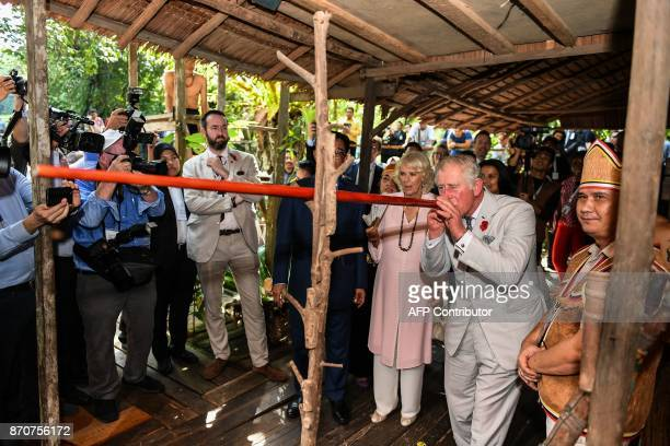 Britain's Prince Charles Prince of Wales tries a blowpipe a weapon of the indigenous people of Sarawak as Camilla Duchess of Cornwall looks on at the...
