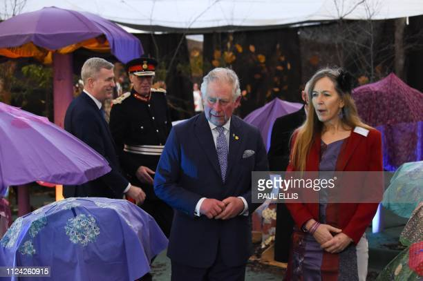 Britain's Prince Charles Prince of Wales walks with Annie Spears the producer of the immersive theatre production The Alice Experience as he tours...