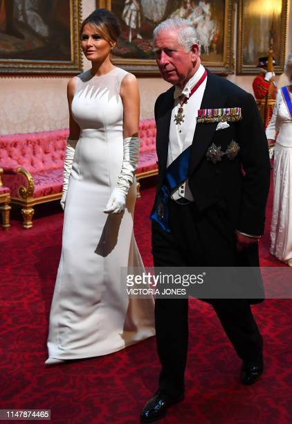 Britain's Prince Charles Prince of Wales walks with US First Lady Melania Trump as they arrive through the East Gallery during a State Banquet in the...