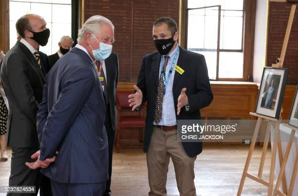 Britain's Prince Charles, Prince of Wales wearing a protective face covering to combat the spread of the coronavirus, is shown photographs of NHS...