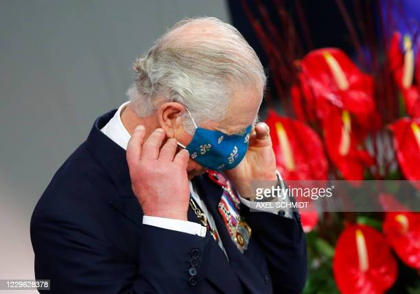 Britain's Prince Charles puts on a protective face mask after a speech at at the Bundestag as he attends an official Remembrance Day commemoration in...