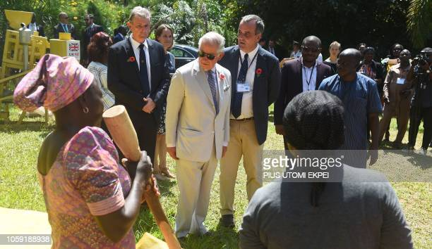 Britain's Prince Charles stands in front of women who demontrate how to pound local food with pestles to secure rural livelihood at the Sarius...