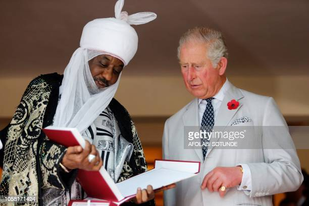 Britain's Prince Charles stands with the Emir of Kano Lamido Sanusi as they look at a book during his meeting with traditional leaders at the British...