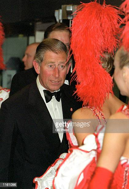 Britain's Prince Charles talks to cancan dancers as he arrives at the premiere of the film Moulin Rouge September 3 2001 in London England