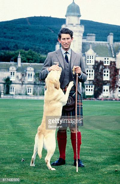 Britain's Prince Charles the Prince of Wales pets Harvey a retriever during photo session 9/17 at Balmoral Castle the Royal residence in Scotland for...