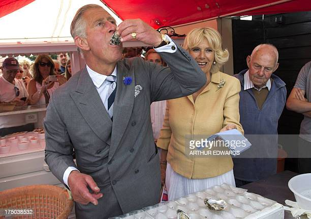 Britain's Prince Charles, the Prince of Wales samples an oyster as Camilla, the Duchess of Cornwall looks on during a visit to the Whitstable Oyster...